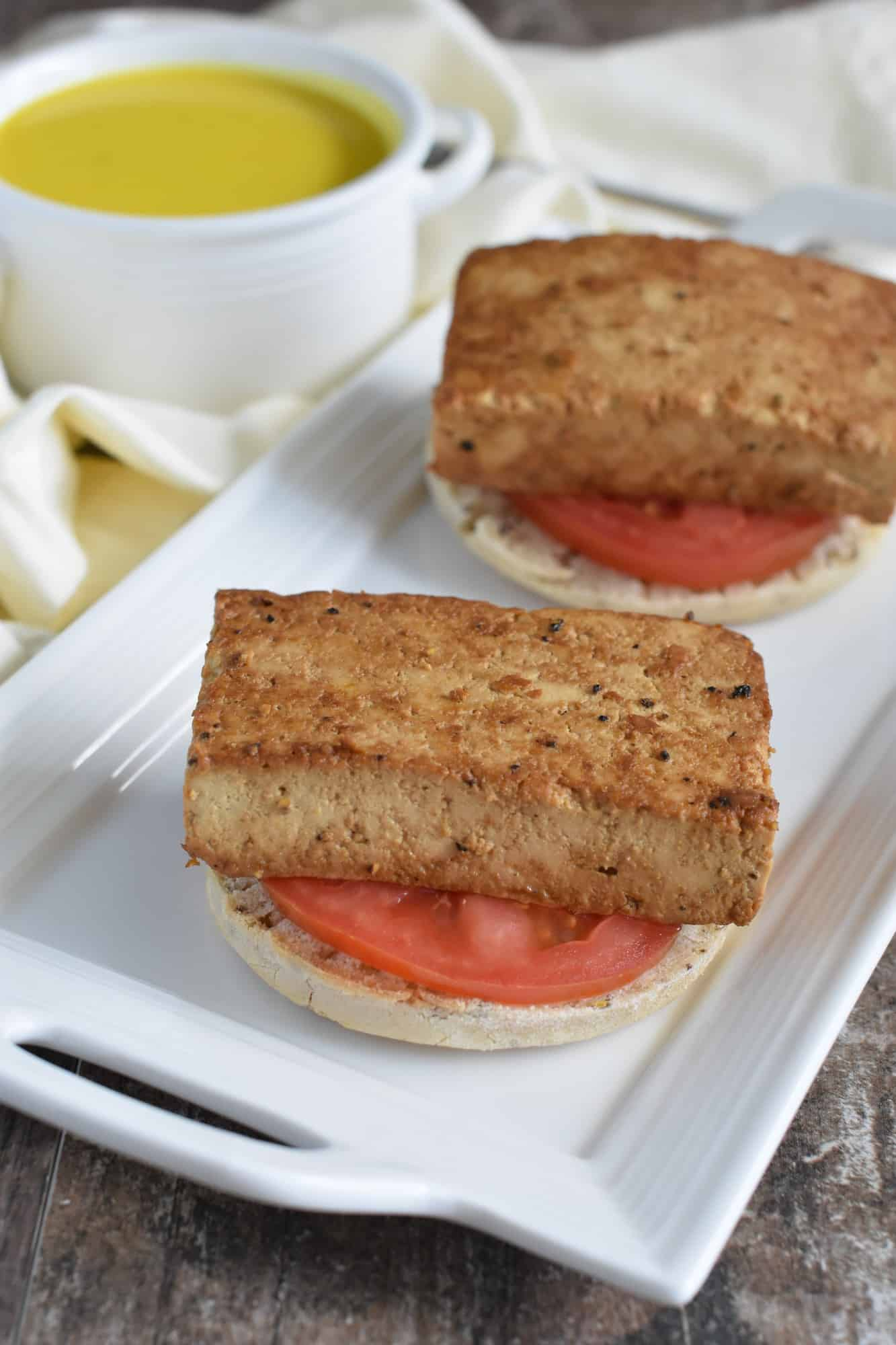 Two English muffins topped with tomato slices and tofu patties
