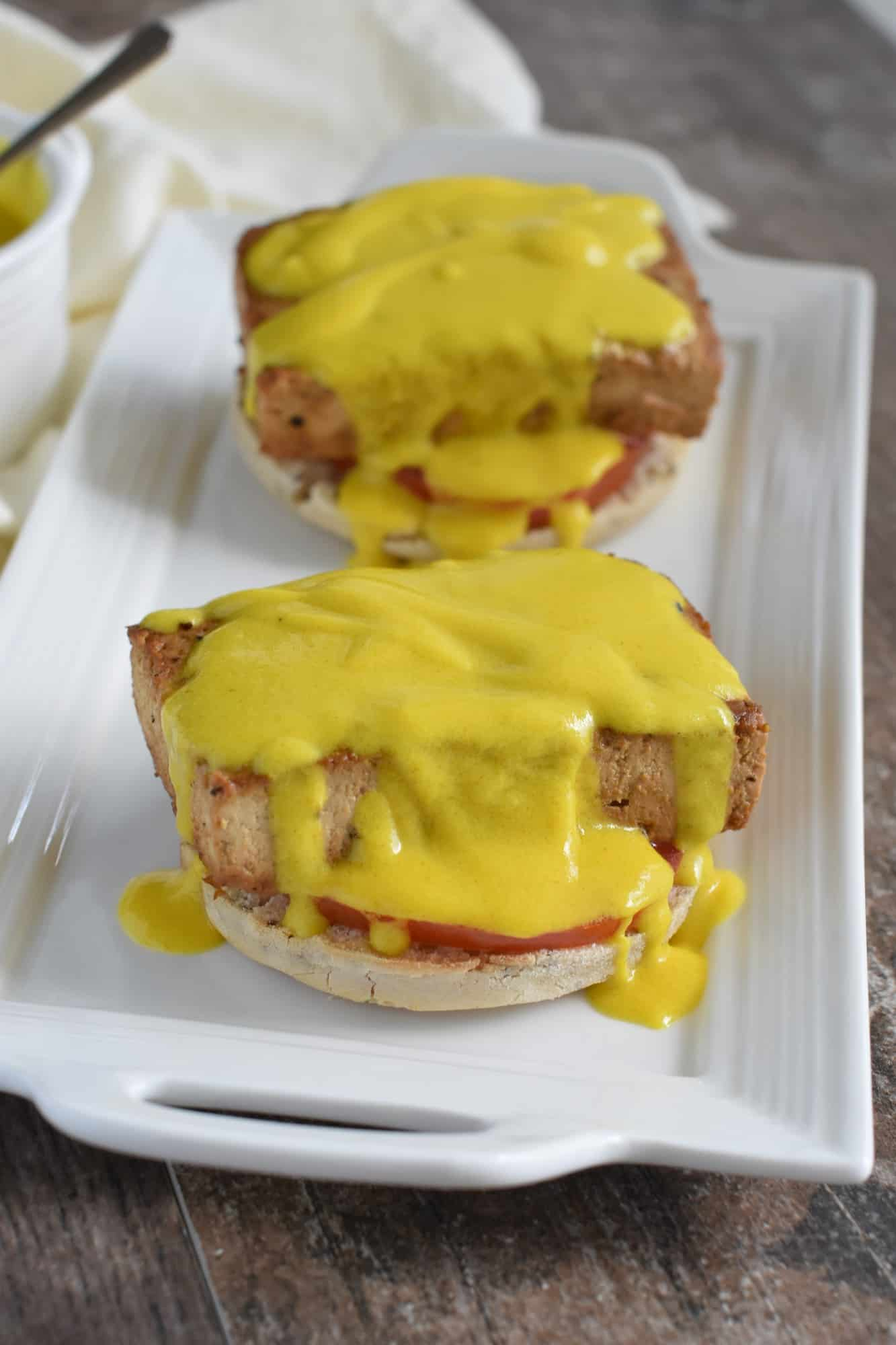 Generous amount of hollandaise poured over tofu patties