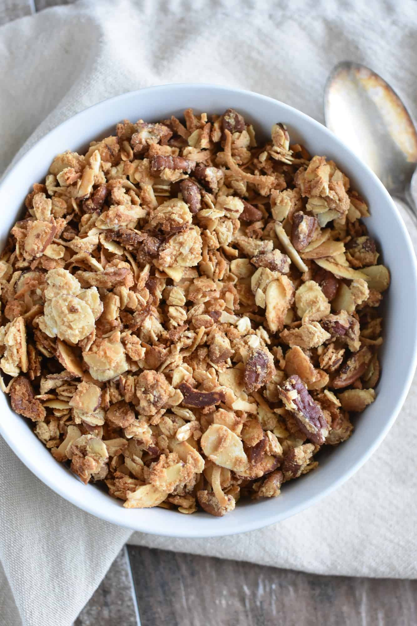 overhead of granola in white bowl with spoon next to it on a kitchen napkin