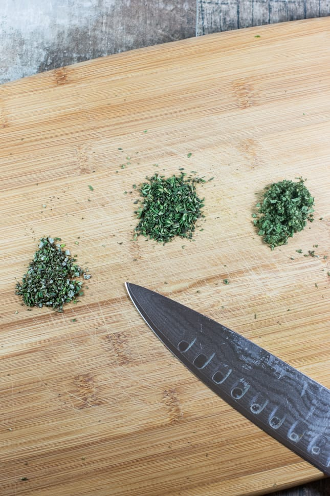 fresh herbs chopped on a cutting board with a knife on it