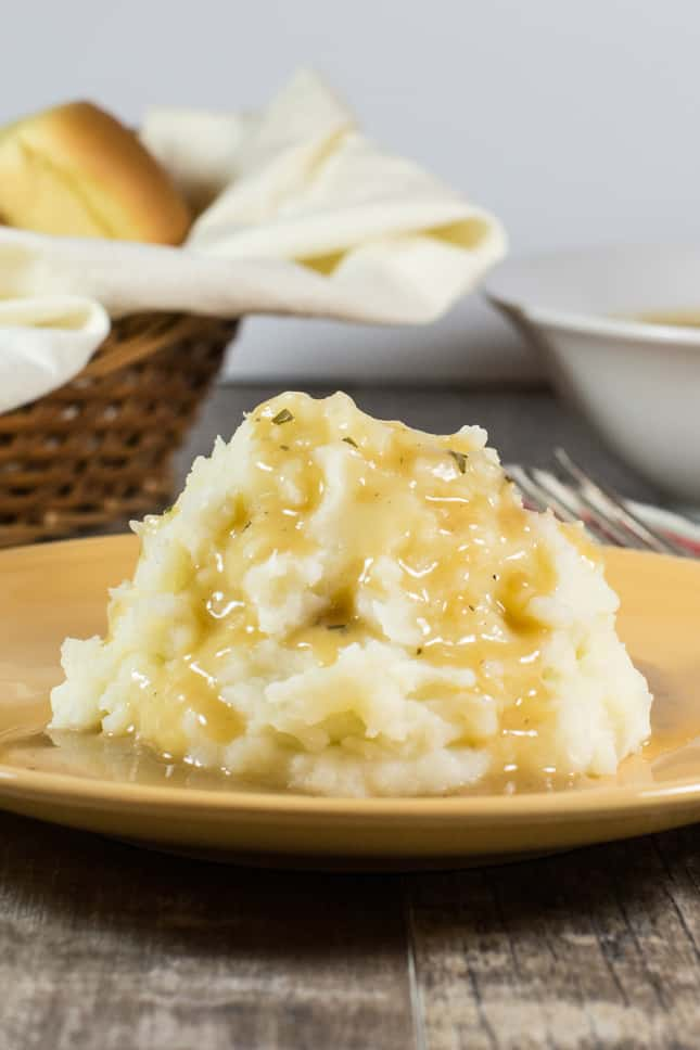 mashed potatoes with gravy on a yellow plate