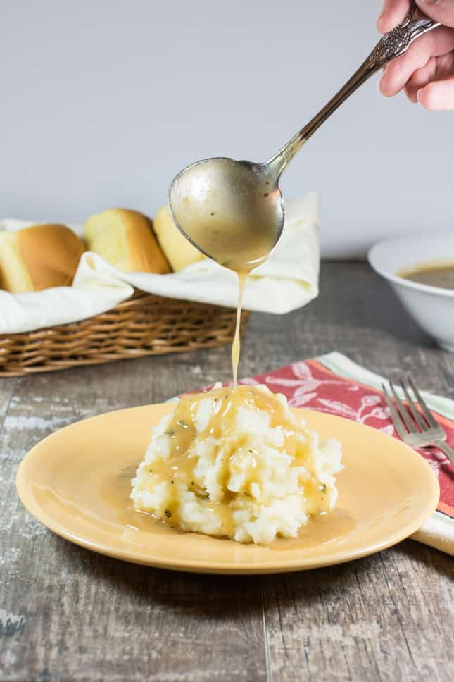 using a ladle to pour gravy onto mashed potatoes on a plate
