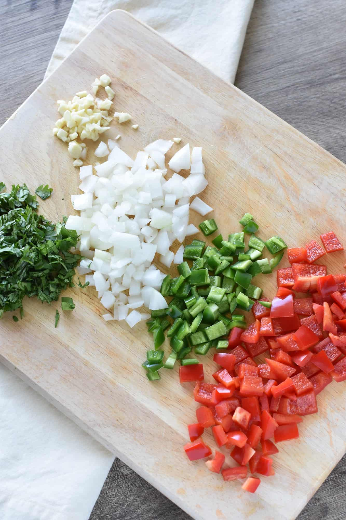 bell pepper, jalapeno, onion, garlic and cilantro chopped on cutting board