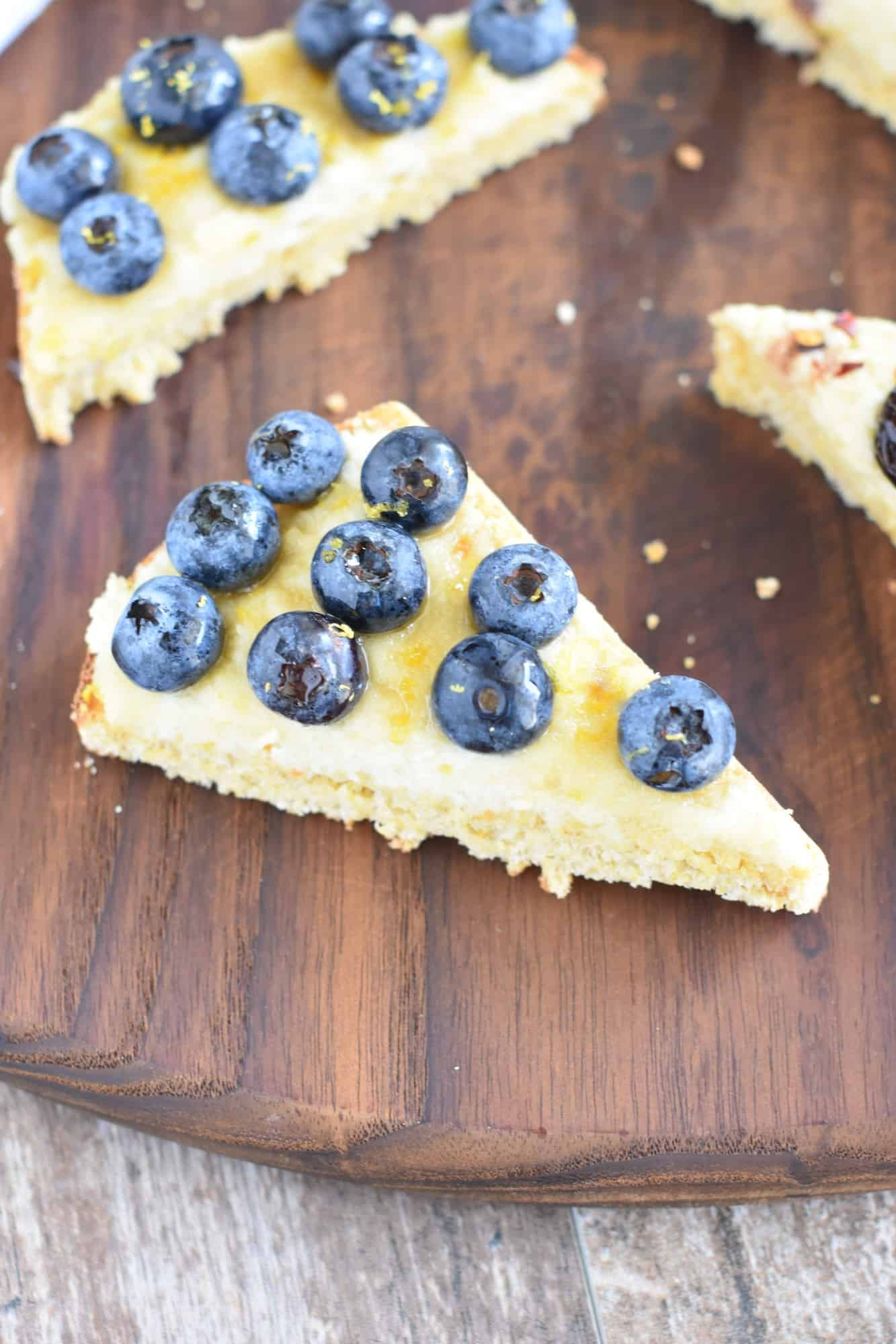 slice of blueberry lemon ricotta toast cut in half on a wooden board