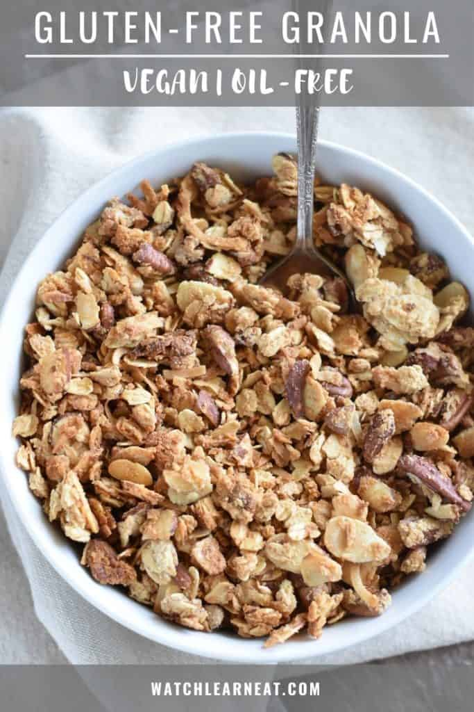 pin showing overhead of granola in a white bowl with a spoon in it