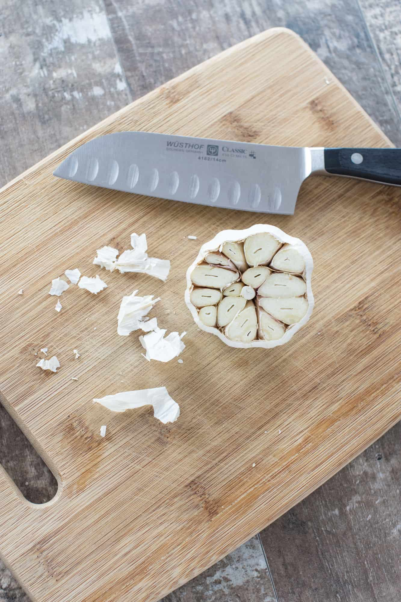 garlic bulb on cutting board with part of the top cut off exposing the cloves