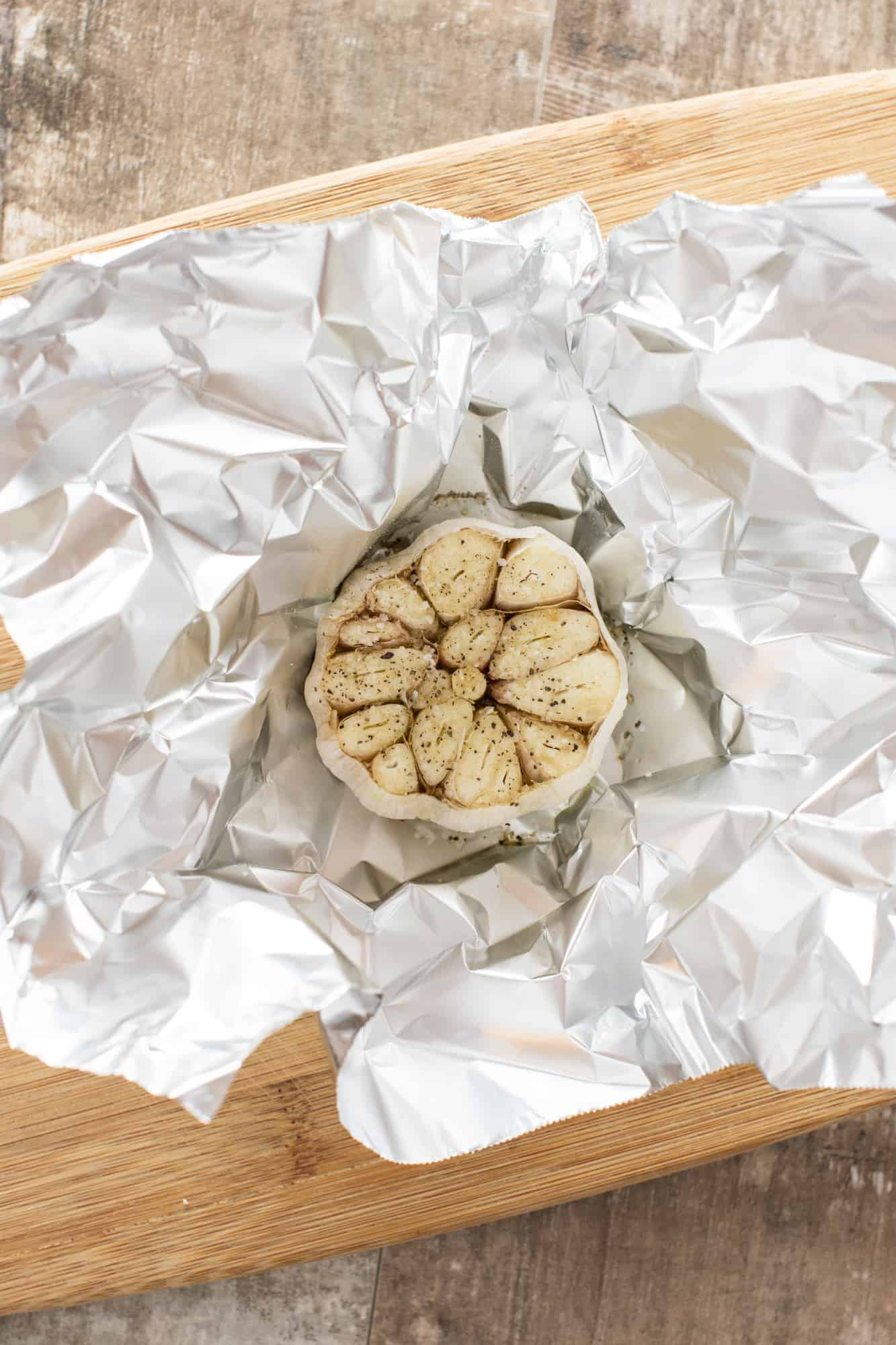 garlic bulb with olive oil, salt and pepper in piece of foil waiting to be wrapped