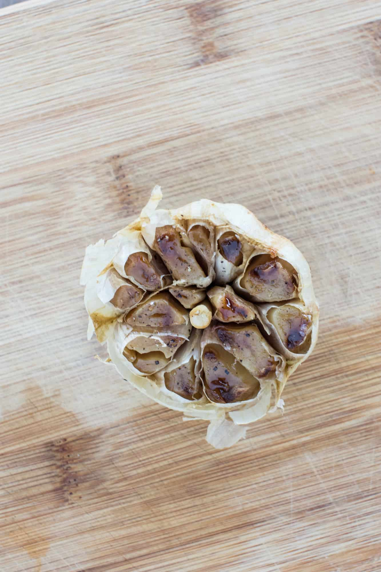 garlic bulb on wooden board after roasting