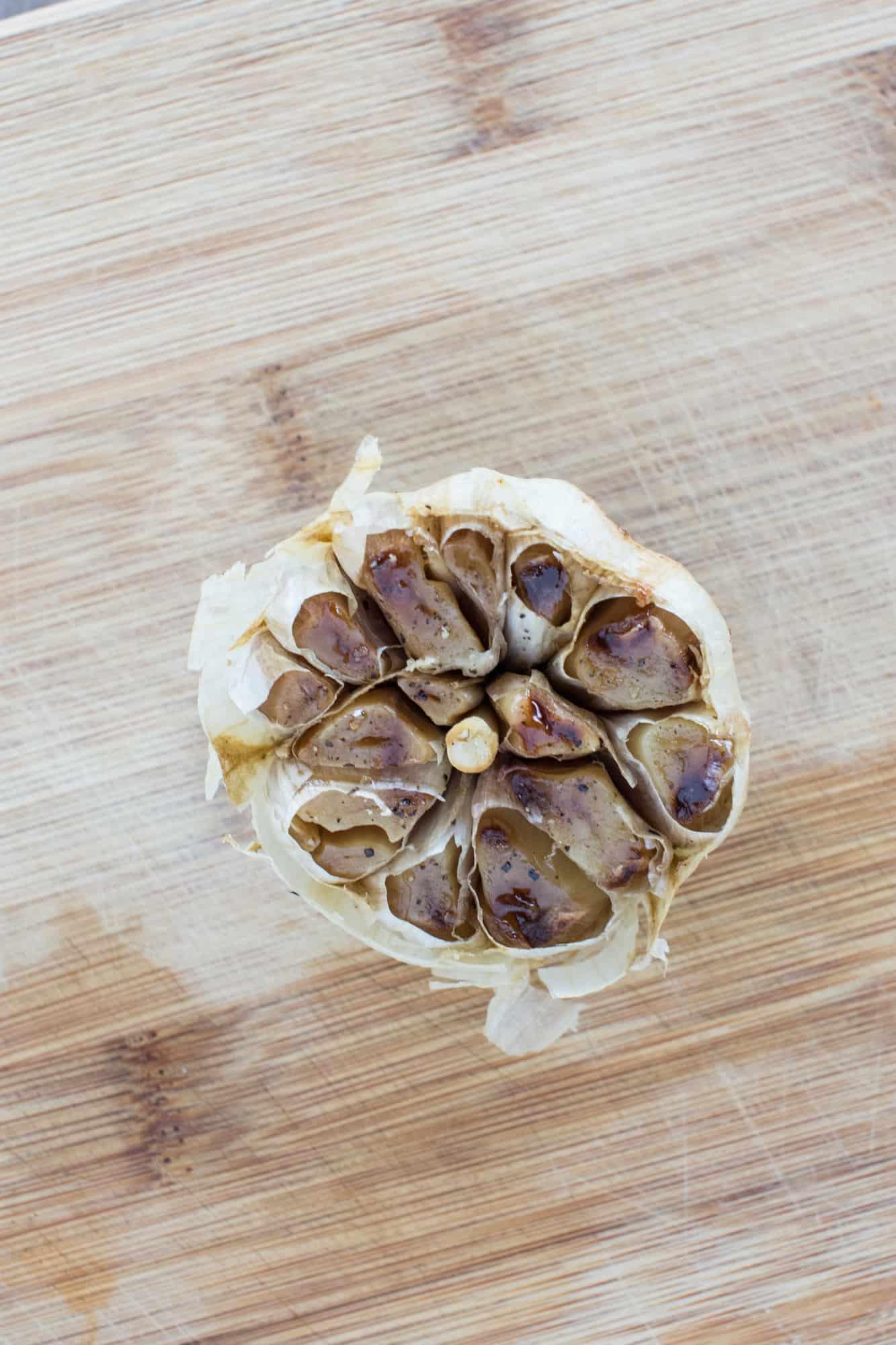 garlic bulb on wooden board after roasting