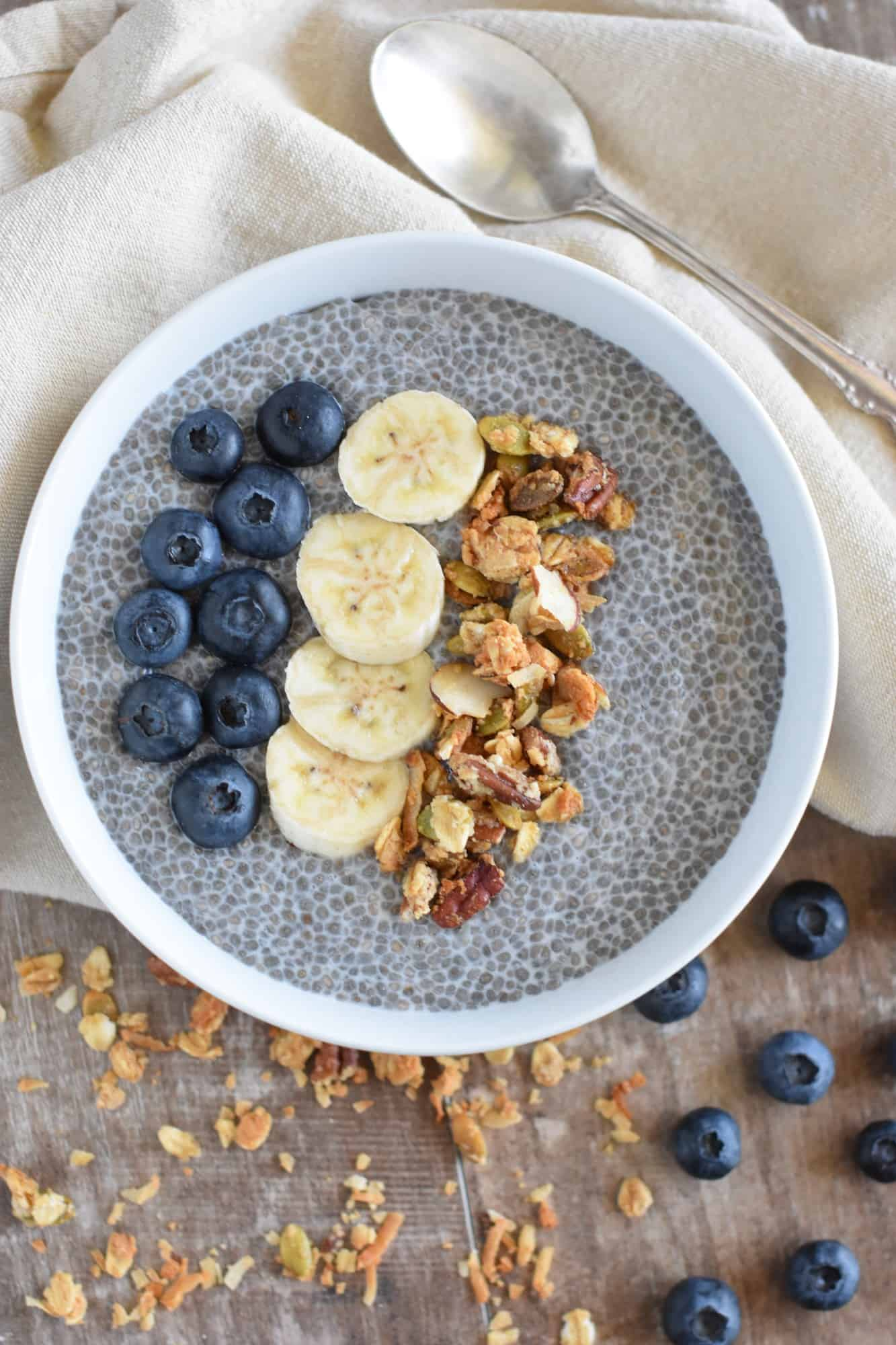 overhead of overnight chia pudding in a white bowl topped with blueberries, bananas and granola with spoon on kitchen napkin behind it