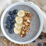 overhead of pudding in a white bowl topped with blueberries, bananas and granola