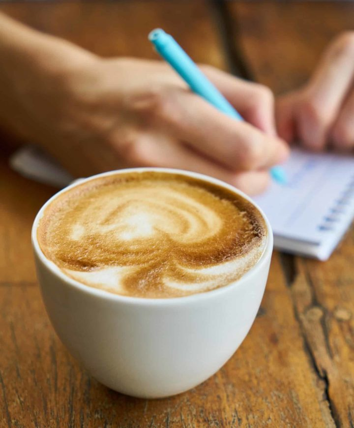 person writing in a small notebook with a latte next to the notebook