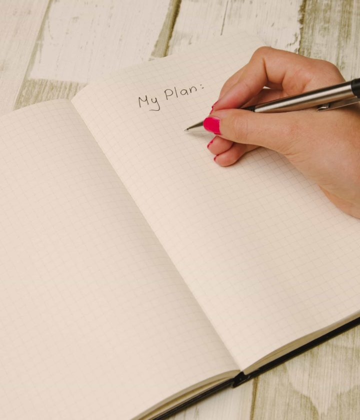 "hand with pen about to write in notebook under the words ""My Plan"""
