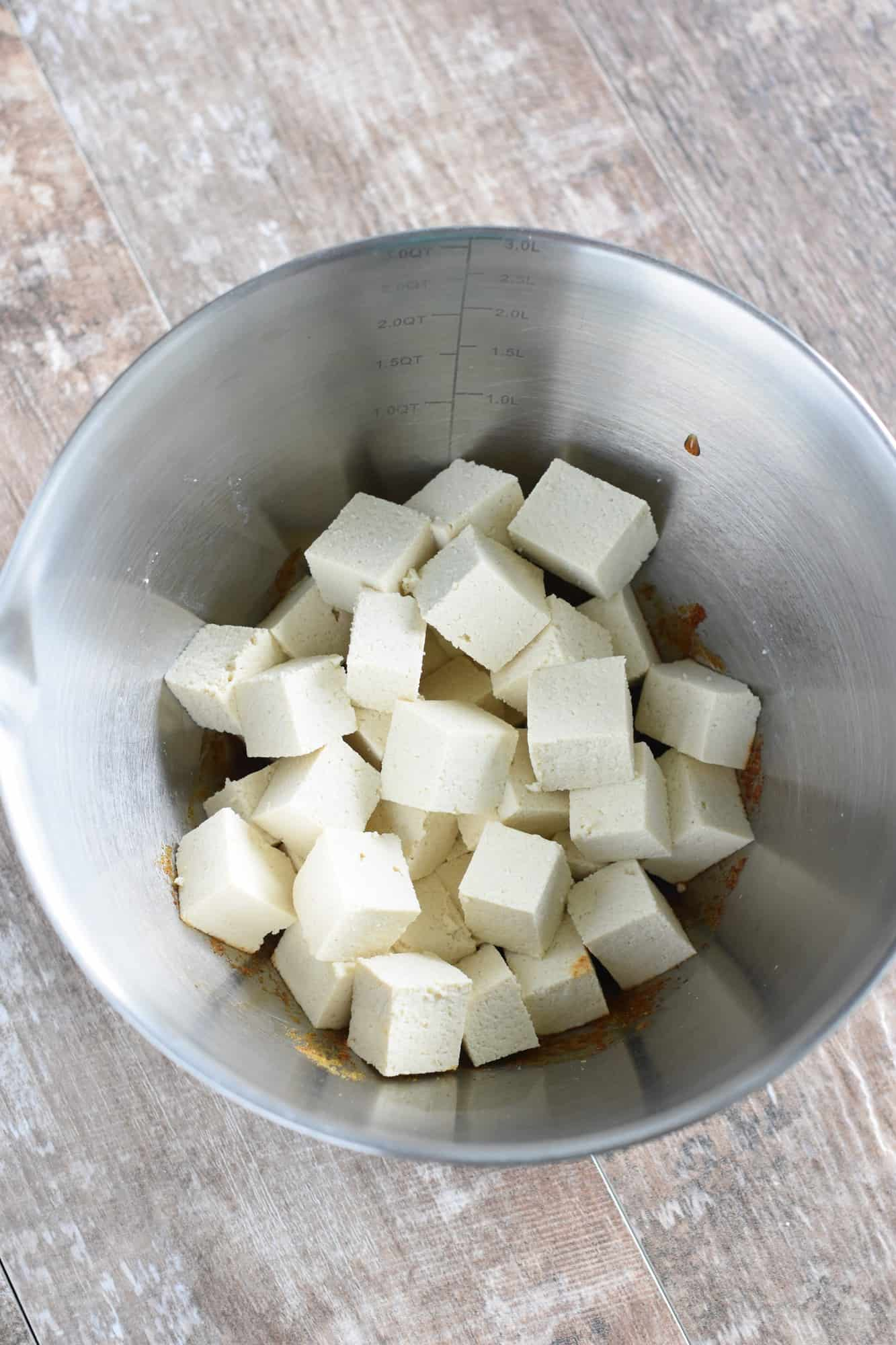 Tofu pieces added to the marinade in the mixing bowl
