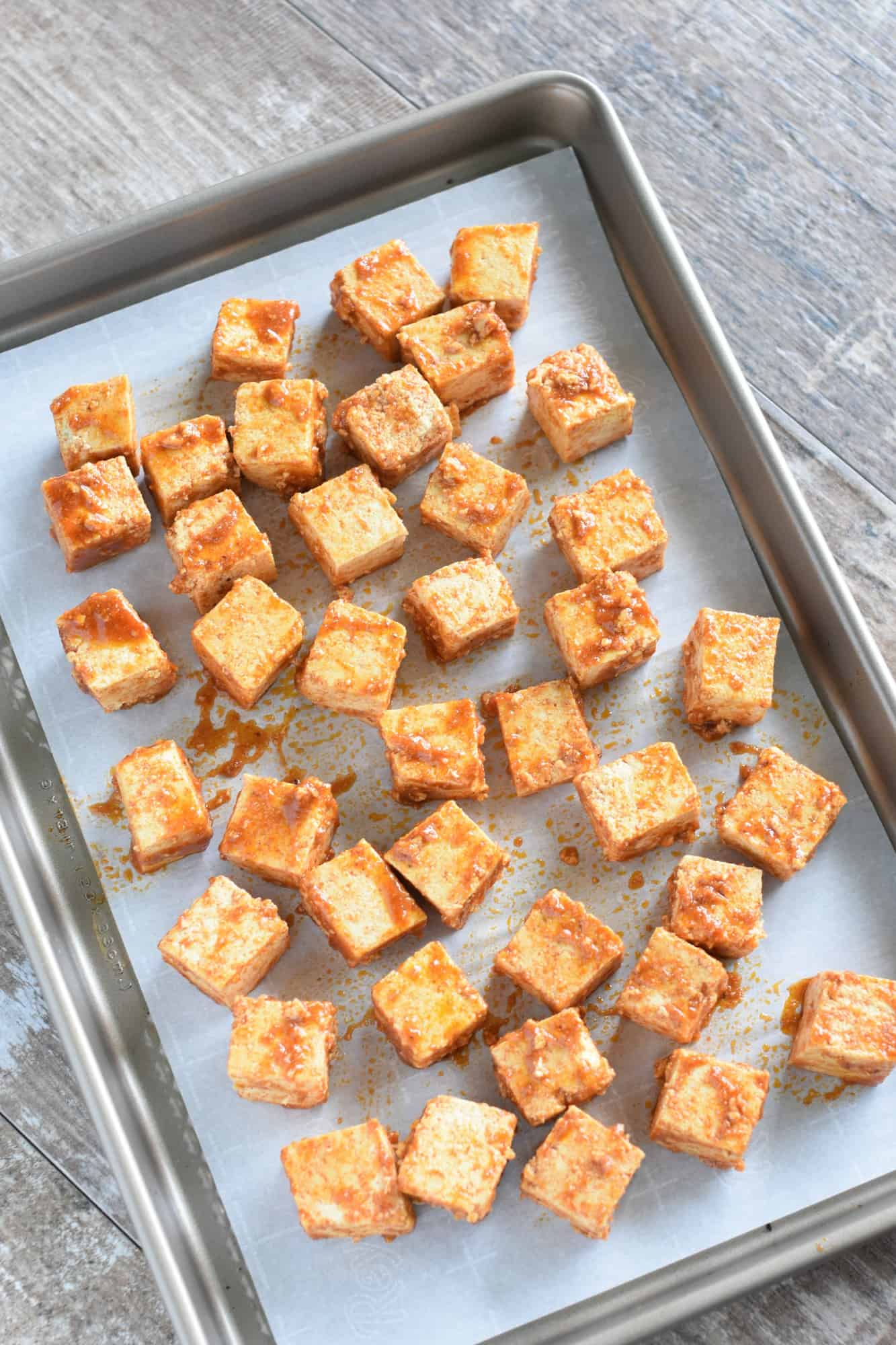 Uncooked tofu pieces on parchment-lined baking sheet