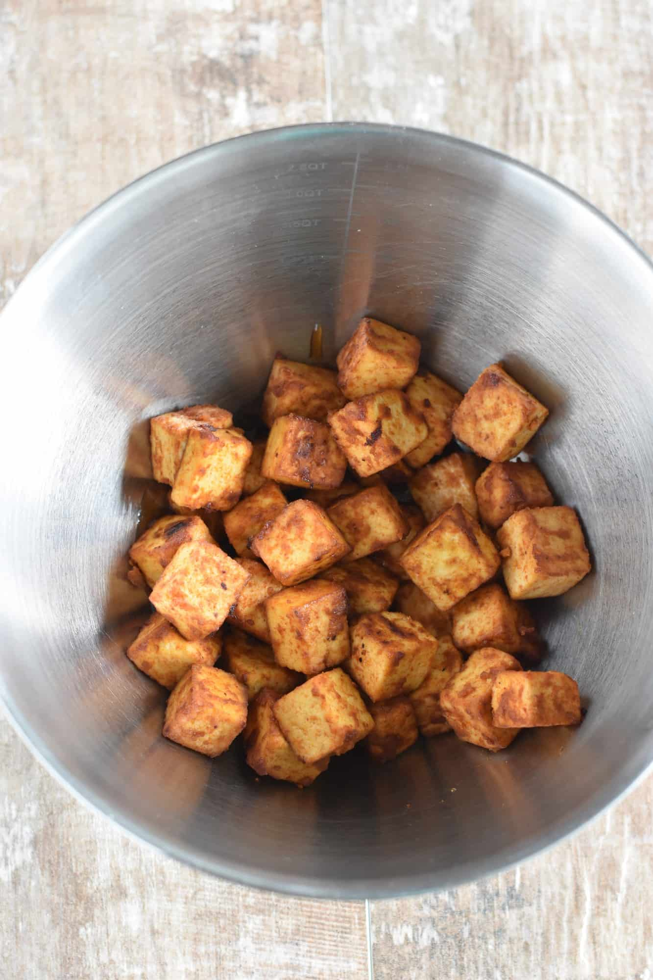 Tofu added to the barbecue sauce in mixing bowl