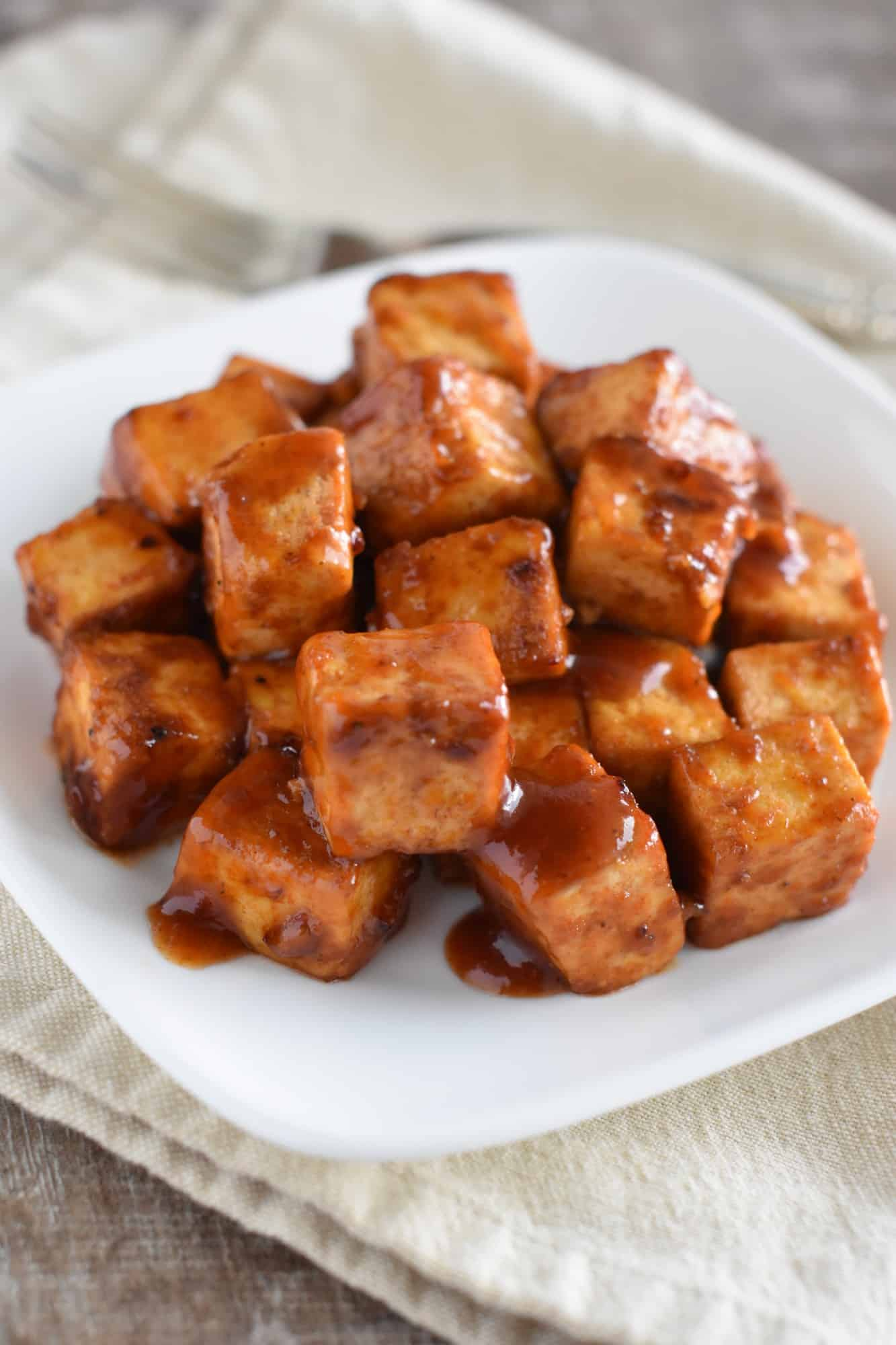 baked bbq tofu on a white plate on a kitchen towel