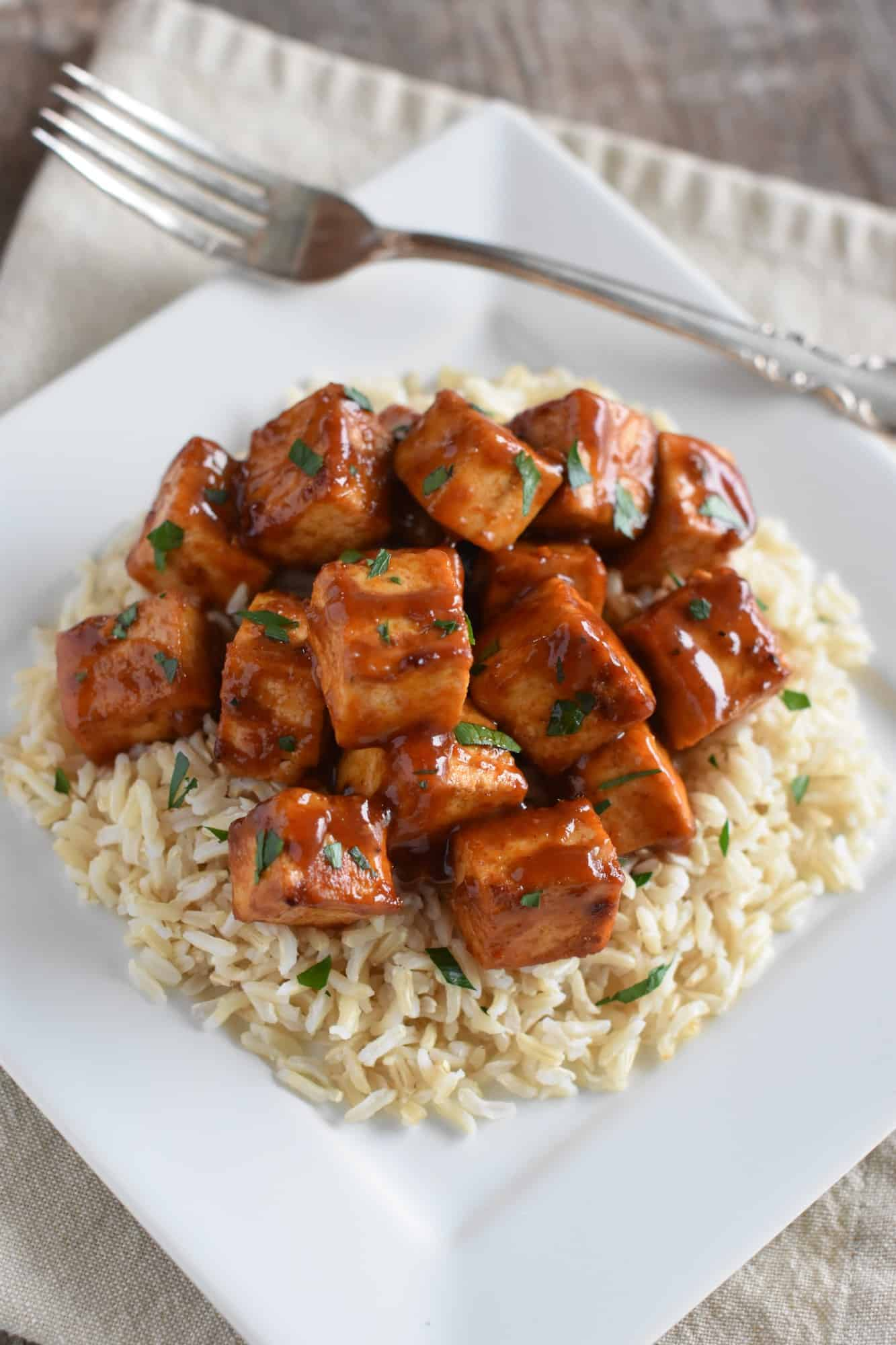 overhead of tofu over rice on a white plate with a fork on the plate