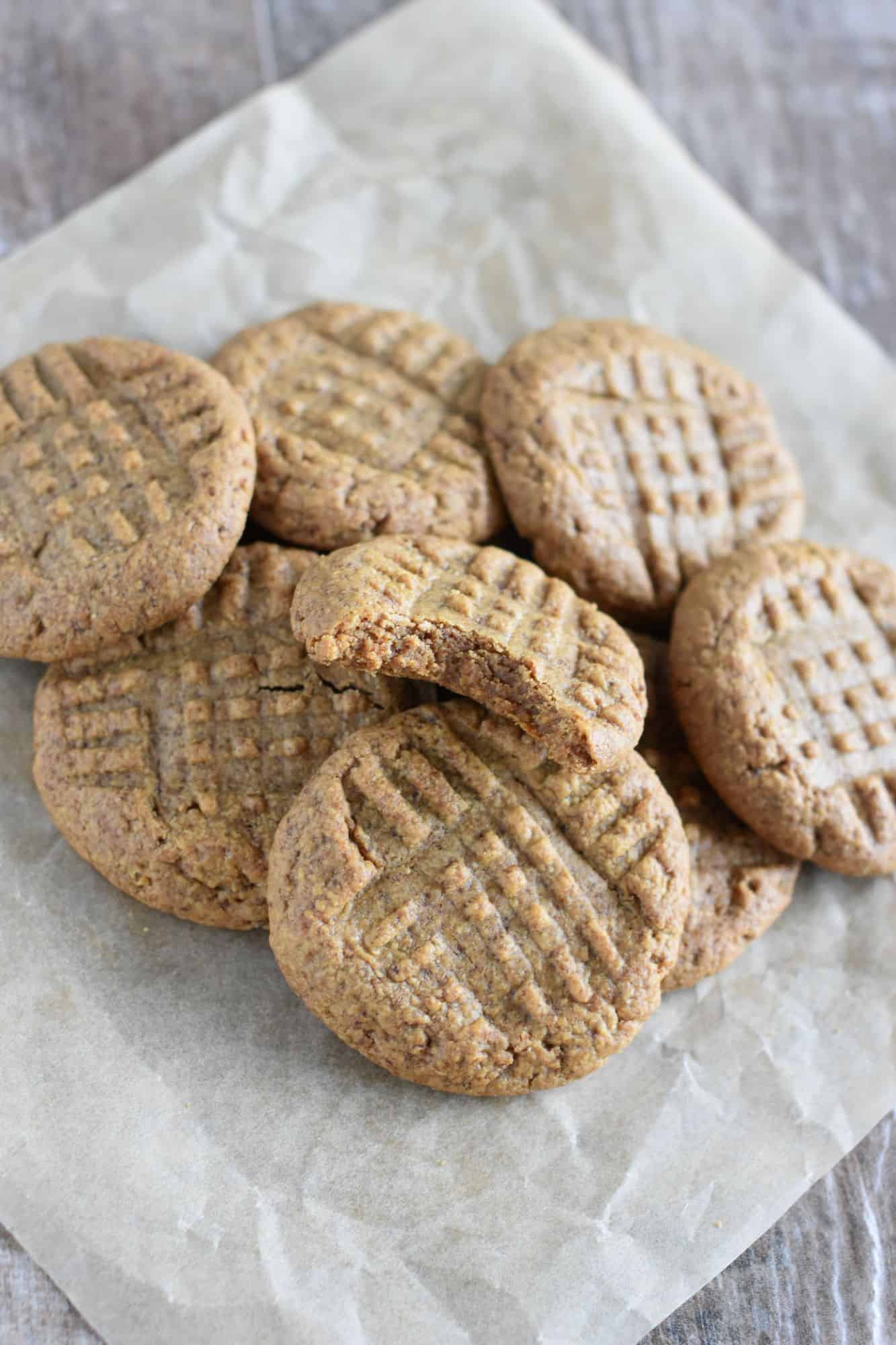 vegan peanut butter cookies on a piece of parchment paper with a bite taken out of one