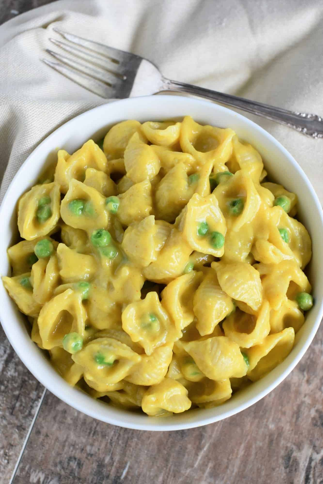 overhead of gluten-free, vegan mac and cheese with peas in a white bowl with a fork behind it