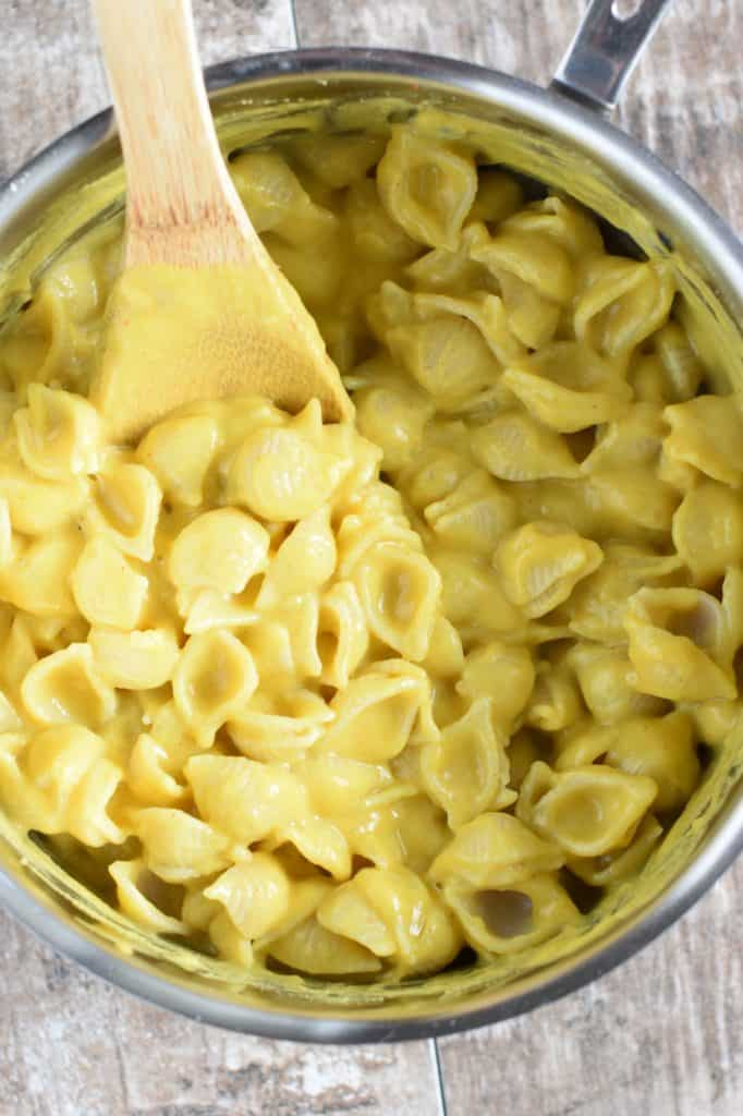 sauce and pasta mixed together in the saucepan with a wooden spoon