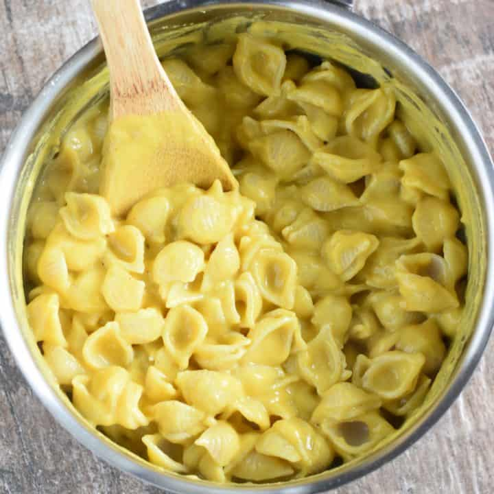 overhead of mac and cheese in a saucepan with a wooden spoon