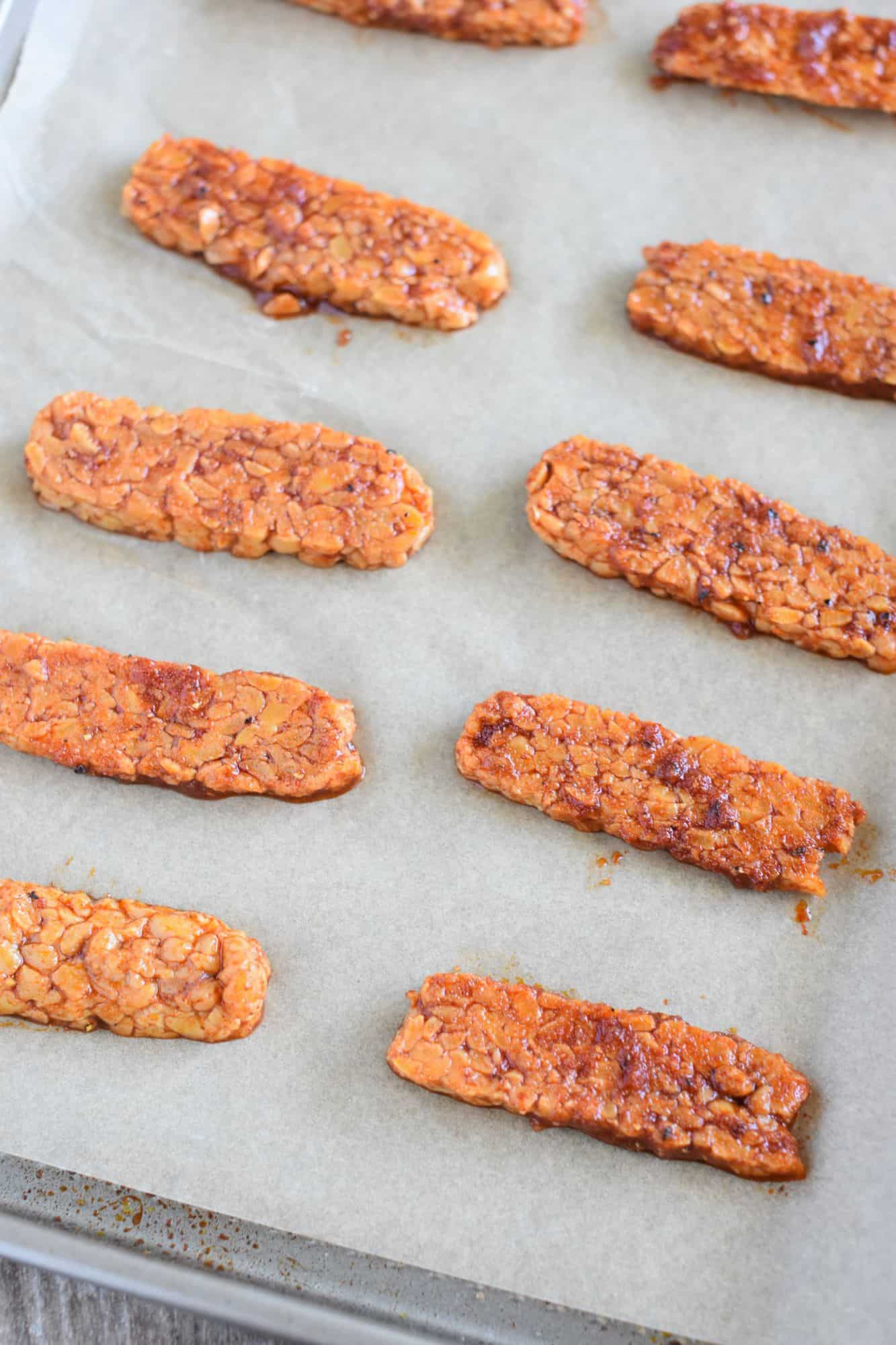 tempeh strips on parchment-lined baking sheet before being cooked