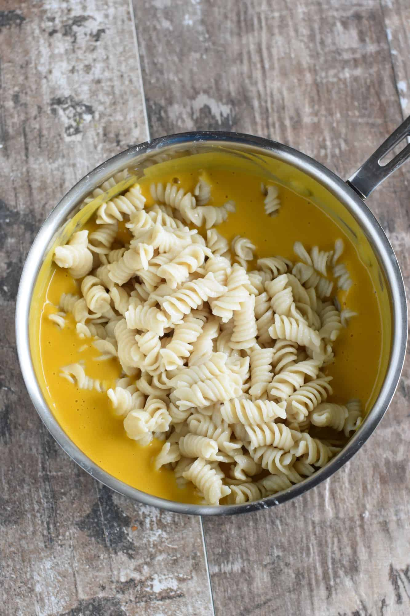 gluten-free pasta added to saucepan with cooked pumpkin sauce