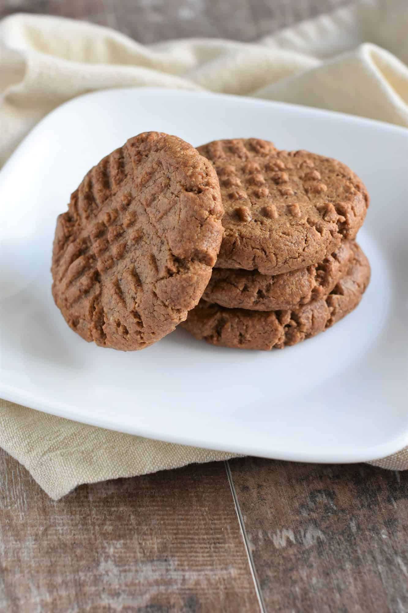 vegan almond butter cookies on a white plate on a kitchen napkin