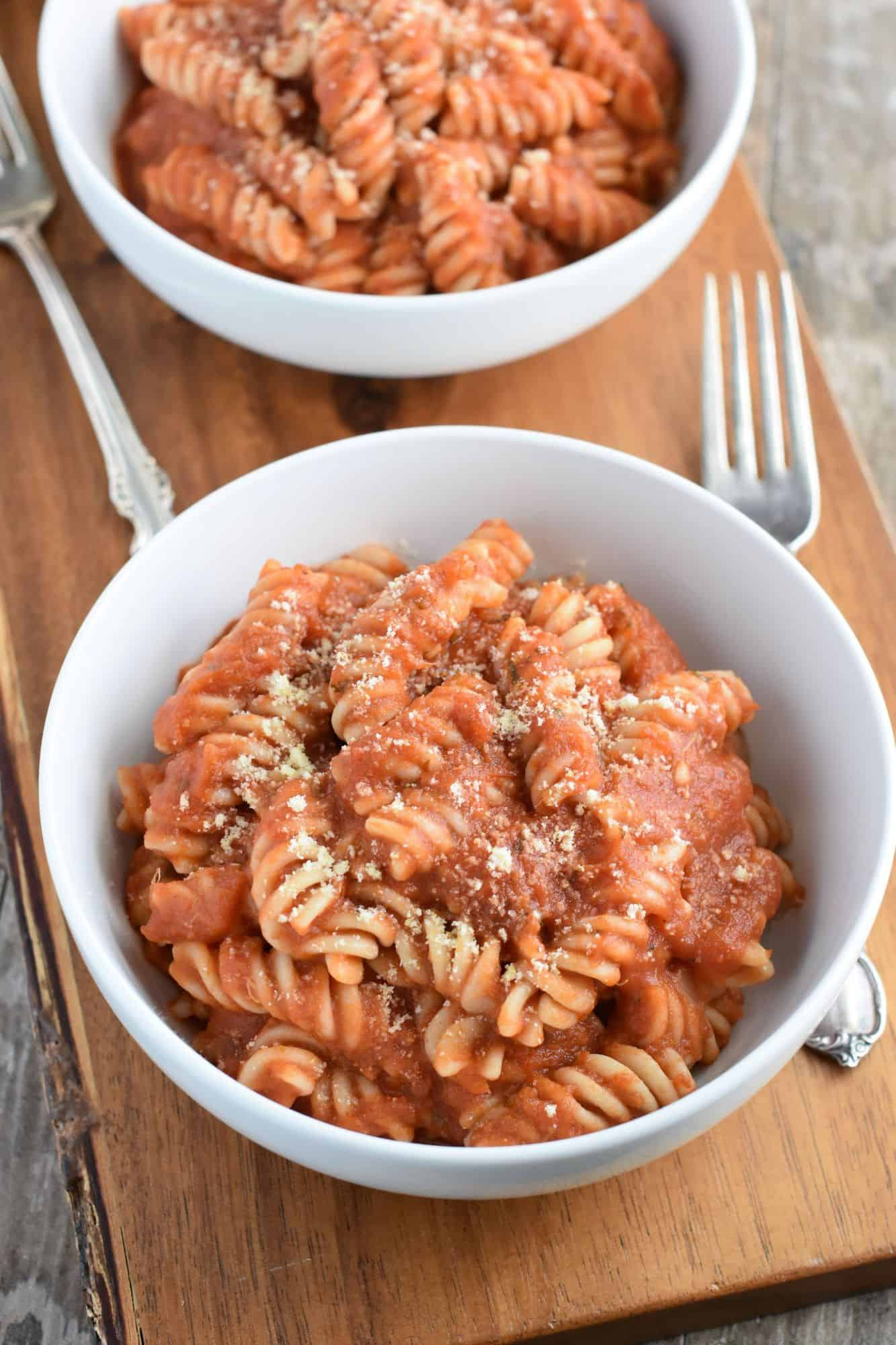 pasta with sauce in white bowl and vegan grated cheese on a wooden board and two forks with another bowl in the background