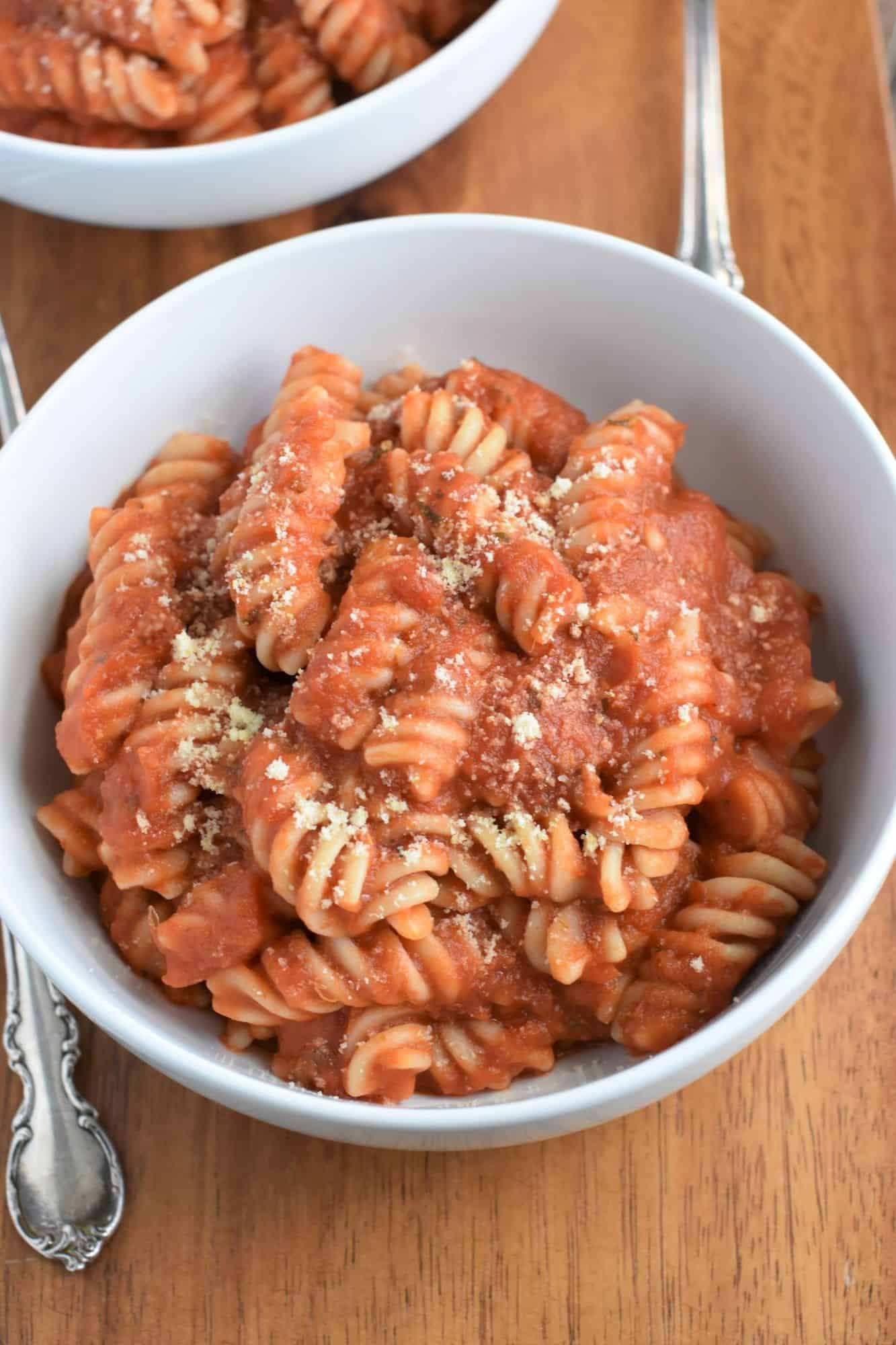 overhead of pasta with sauce in a white bowl with vegan grated cheese