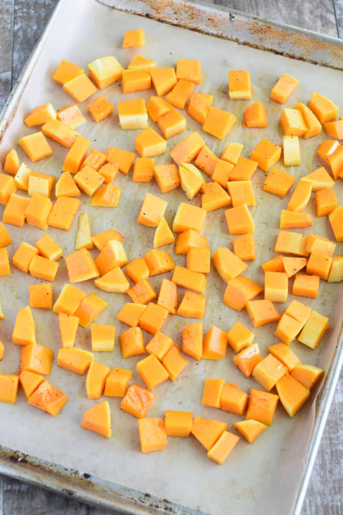 butternut squash cubes with olive oil and seasoned with salt and pepper on baking sheet