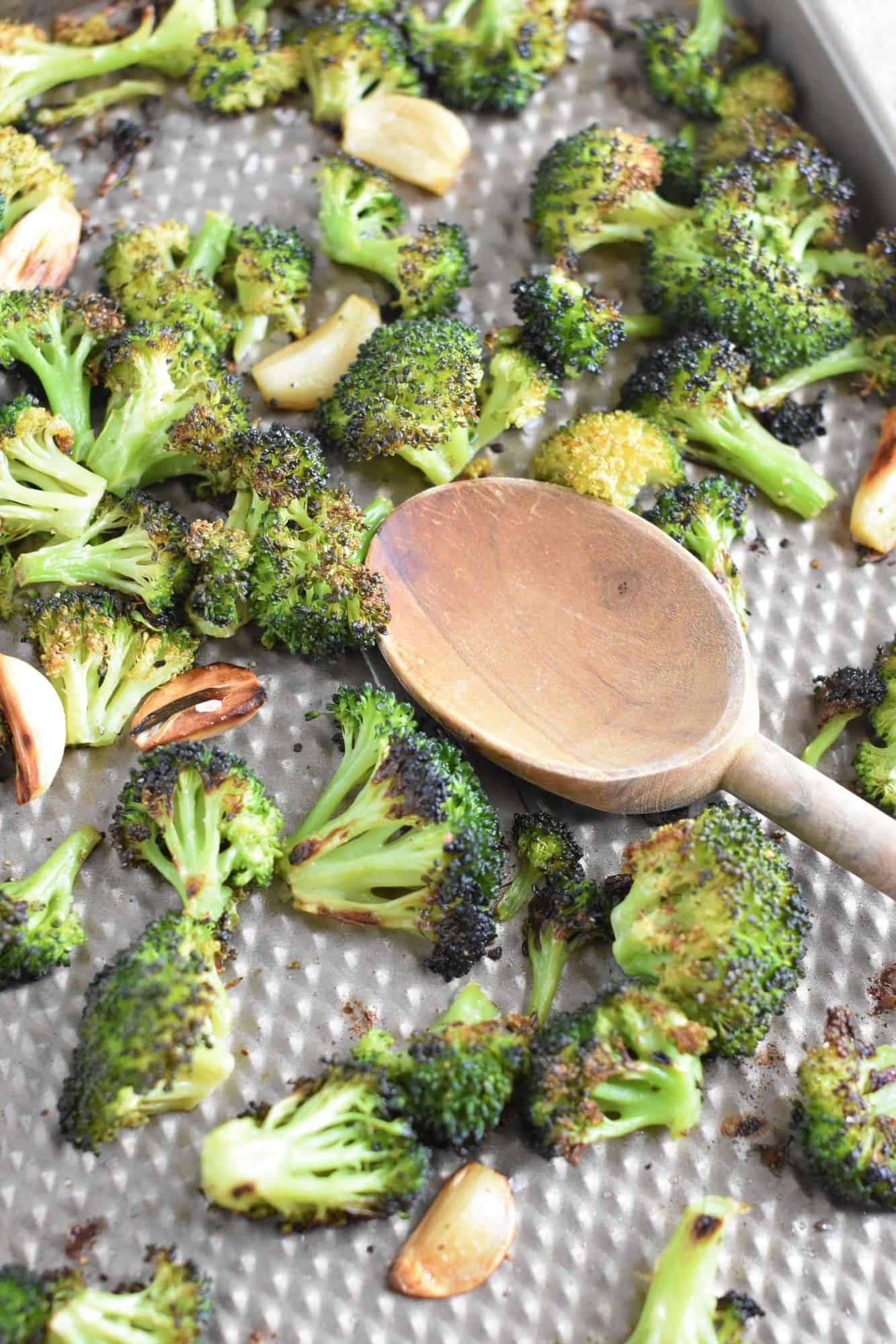 broccoli and garlic on baking sheet with wooden spoon after being cooked