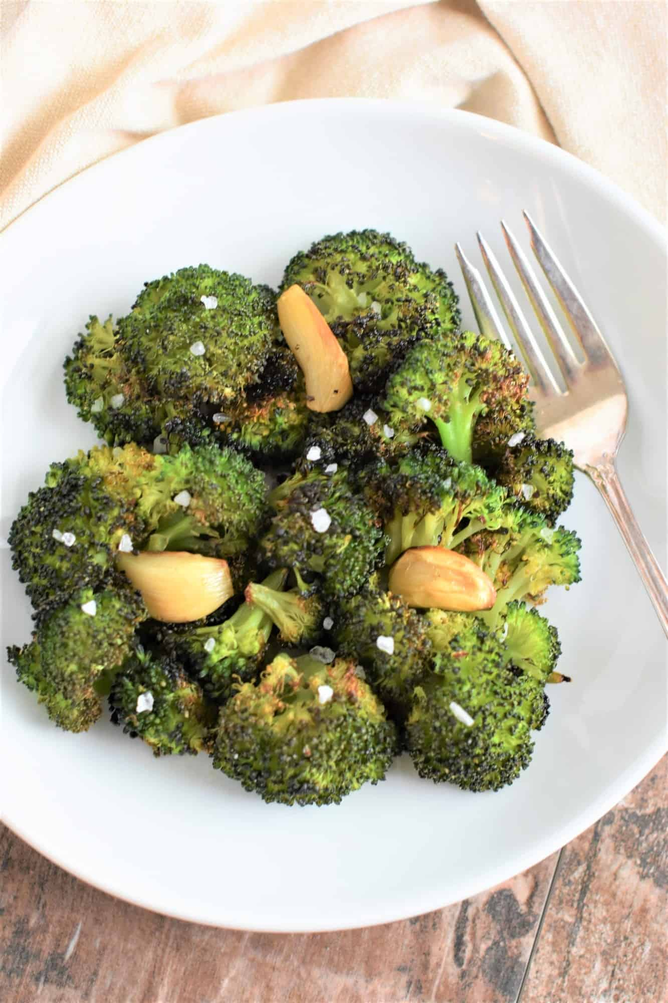 overhead of roasted broccoli with garlic garnished with salt on white plate