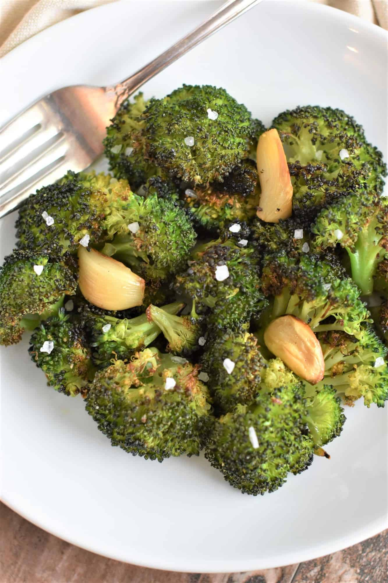broccoli garnished with coarse sea salt on white plate with fork