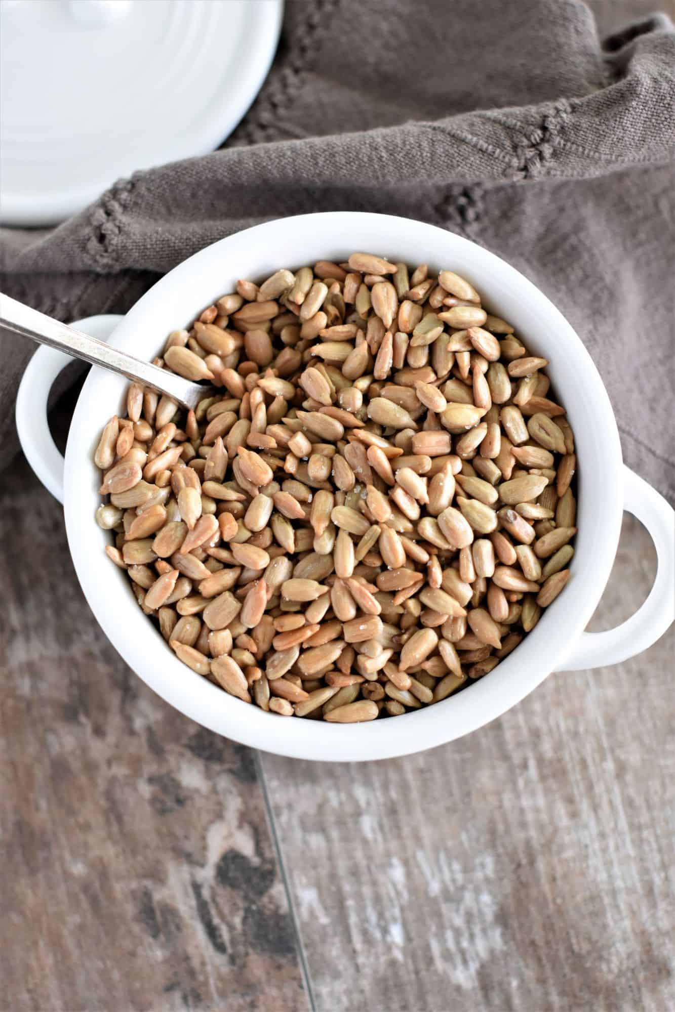 overhead of roasted sunflower seeds in white bowl with spoon