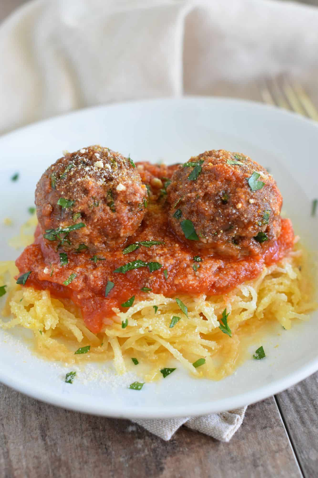 two meatballs with sauce on spaghetti squash on white plate