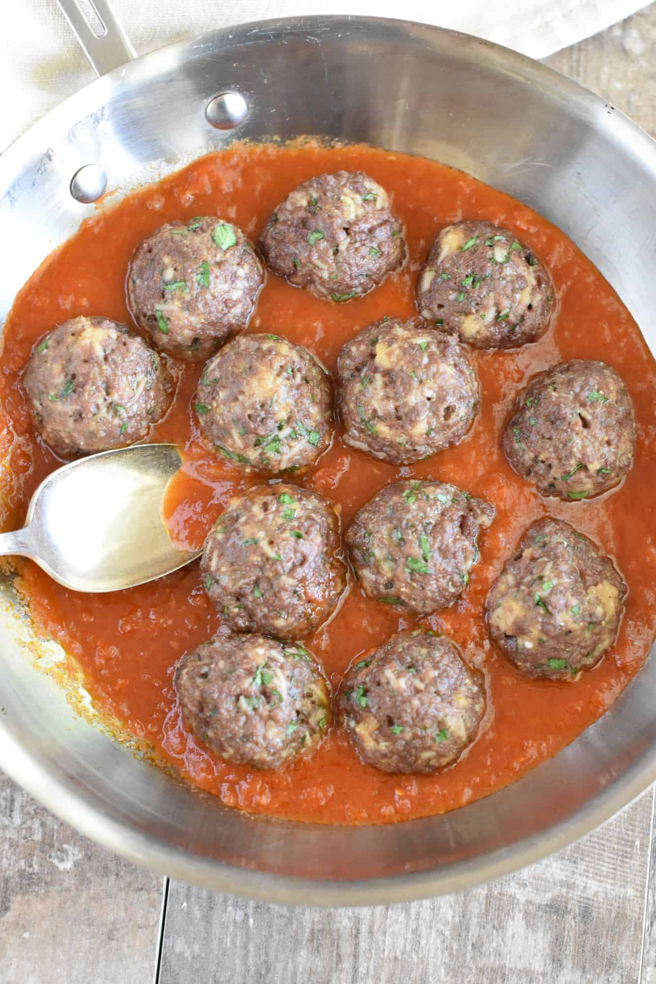 meatballs in skillet in sauce with spoon getting some sauce