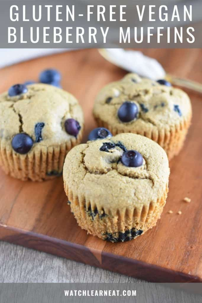 pin showing three blueberry muffins on a wood board with spreading knife in the background with some vegan butter on it