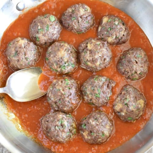 close-up overhead of meatballs in sauce in saucepan with a spoon in it