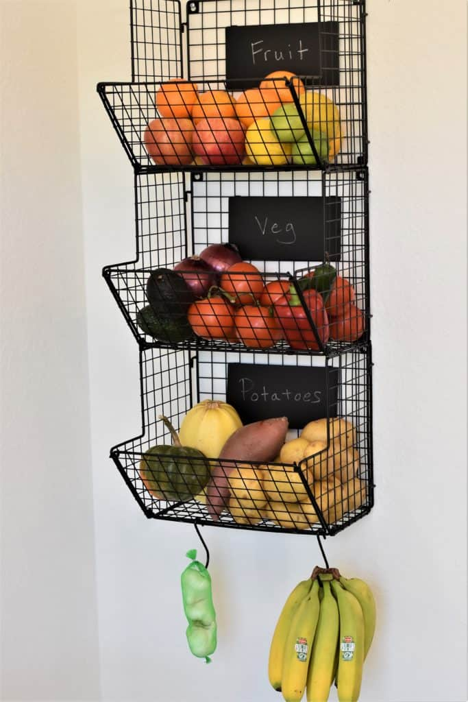 variety of fruits and vegetables in wire hanging rack