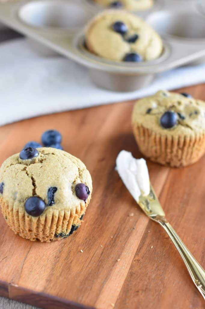 two muffins on a wood board with a spreading knife with some butter on it