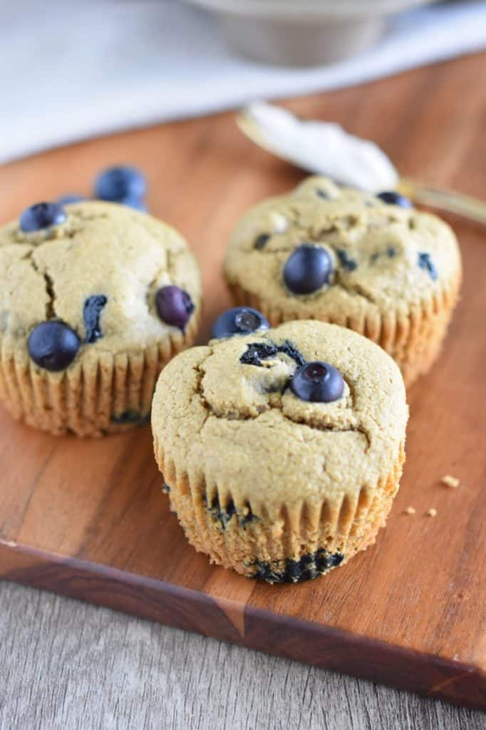 front view of three muffins on a wood board with spreading knife with butter on it behind them