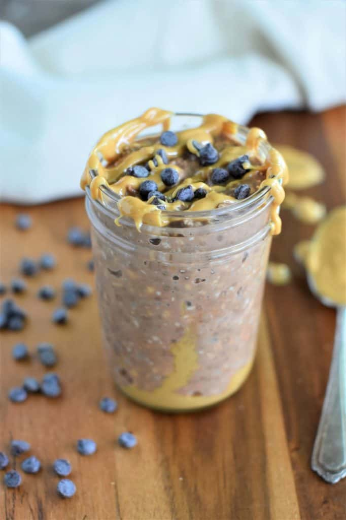 front view of mason jar of overnight oats topped with peanut butter and chocolate chips