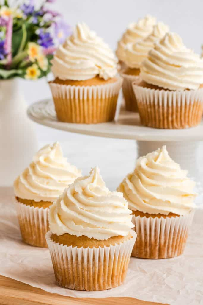 3 frosted cupcakes on a piece of parchment with more on a raised cake plate behind them