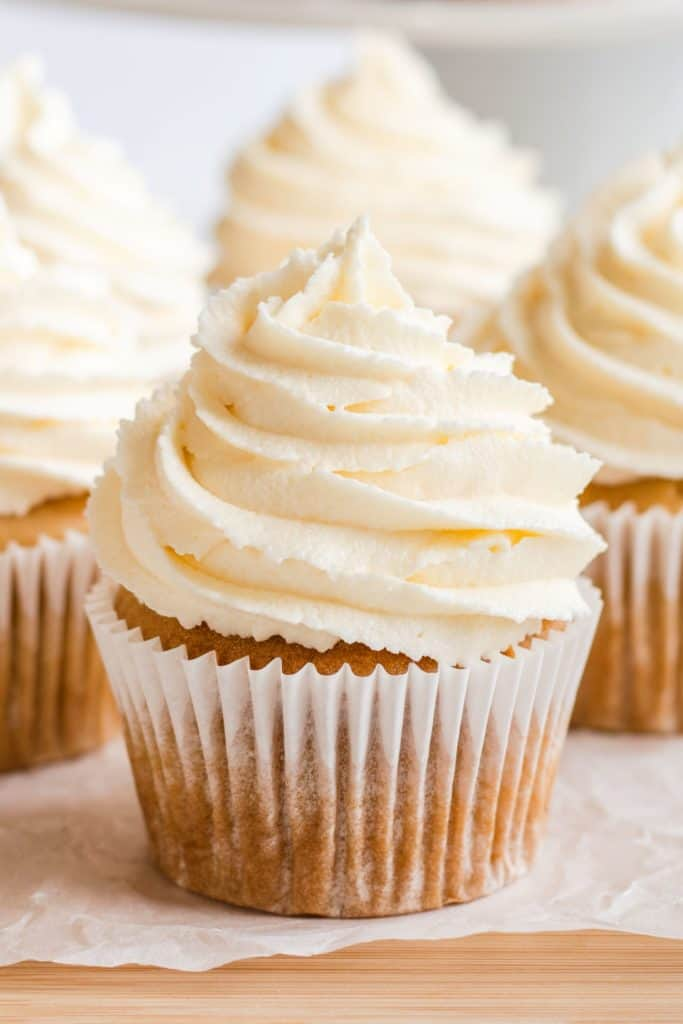 close-up of one frosted cupcake with some more blurred out behind it