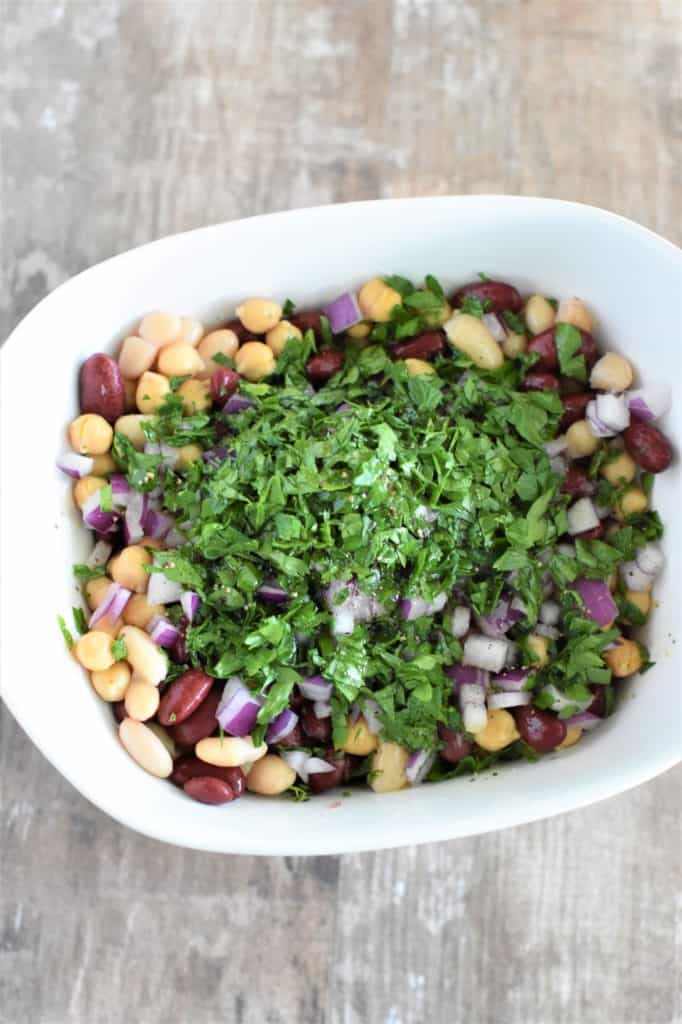 red onion, cilantro and dressing added to beans in white mixing bowl