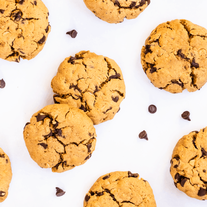 close-up overhead of cookies on a white surface with chocolate chips around