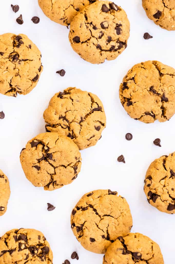 overhead of cookies on a white surface with chocolate chips around them