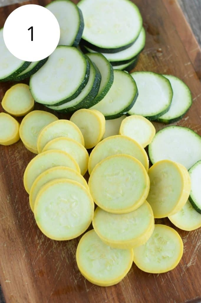 raw yellow squash and green zucchini cut into circles on a wooden board